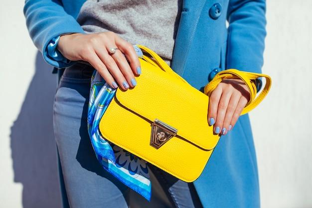 スタイリッシュな黄色のハンドバッグを保持し、流行の青いコートを着ている若い女性。春の女性の服やアクセサリー。ファッション。 2021年の色