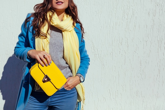 Young woman holding stylish yellow handbag and wearing trendy blue coat. spring female clothes and accessories. fashion. color of 2021