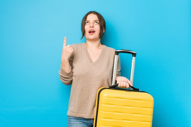 Young woman holding a suitcase pointing upside with open mouth.