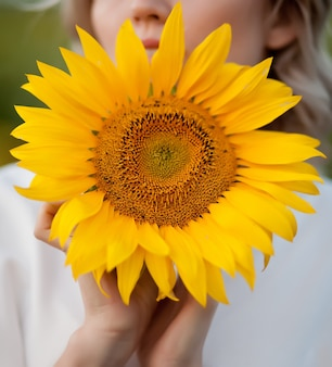 Young woman holding a sunflower in a hand