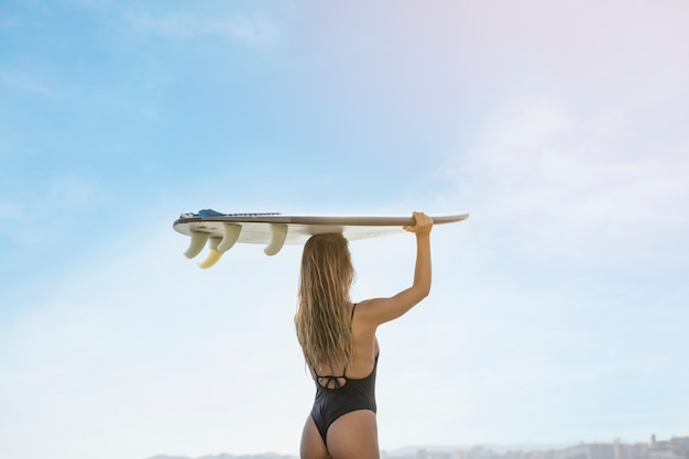 Young woman holding surfboard on head