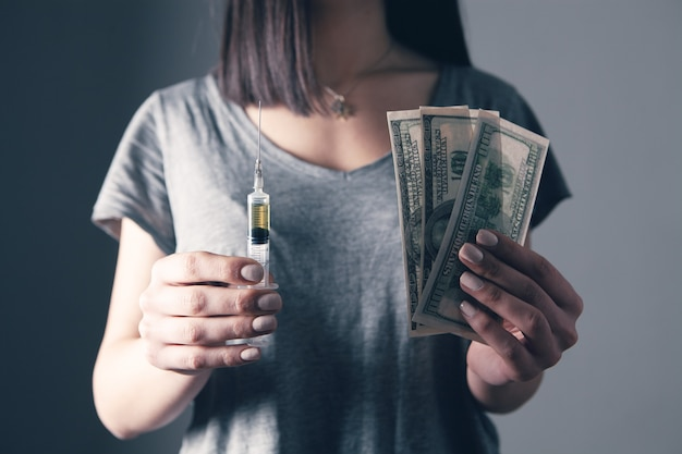 Young woman holding syringe and money
