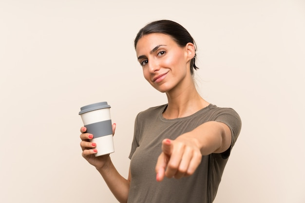 Young woman holding a take away coffee points finger at you with a confident expression