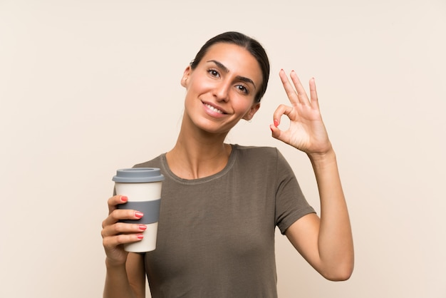 Young woman holding a take away coffee showing ok sign with fingers