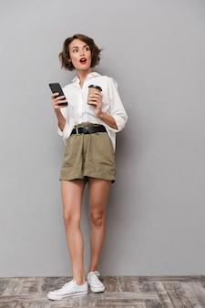 テイクアウトコーヒーを保持し、スマートフォンを使用して、灰色の壁に隔離の若い女性