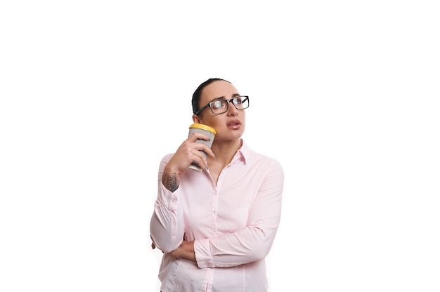 Young  woman holding a takeaway paper cup near her chin and looking up on white background with a pensive look