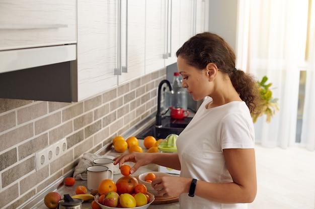 手にみかんを持って、台所で果物と一緒にそれをボルに入れる若い女性。ビーガンコンセプト