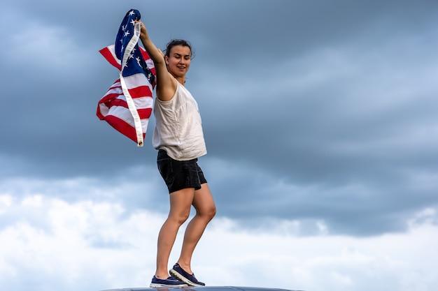 Молодая женщина держит флаг америки на фоне неба.