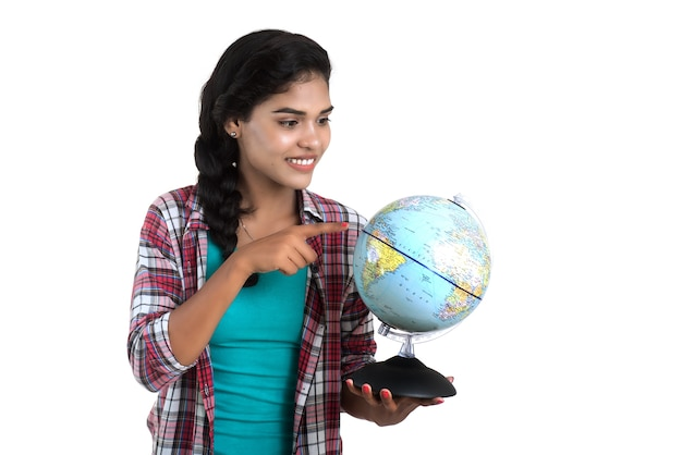 Молодая женщина держит глобус мира и позирует.