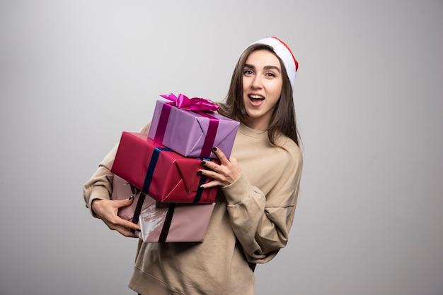 크리스마스 선물 세 상자를 들고하는 젊은 여자. 무료 사진