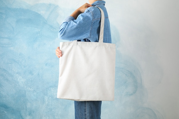 Young woman holding tote bag against blue
