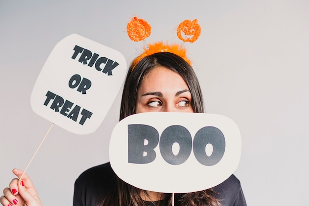 Young woman holding a trick or treat and a boo sign. wearing a black and white skeleton costume. halloween concept. indoors. lifestyle