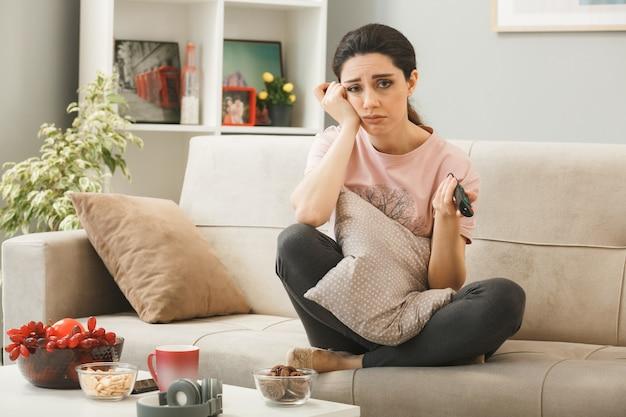リビングルームのコーヒーテーブルの後ろのソファに座ってテレビのリモコンを保持している若い女性