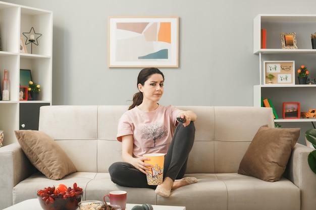 Молодая женщина, держащая пульт от телевизора, сидит на диване за журнальным столиком в гостиной