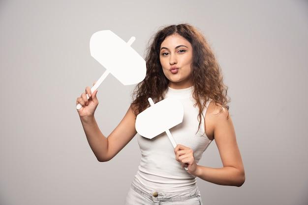 Giovane donna che tiene due manifesti bianchi in bianco. foto di alta qualità