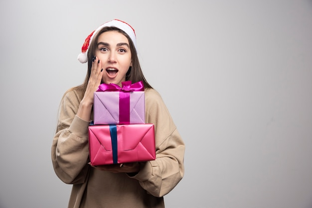 Young woman holding two christmas presents .