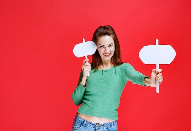 Giovane donna che tiene in entrambe le mani due schede informative o punti salienti della posizione