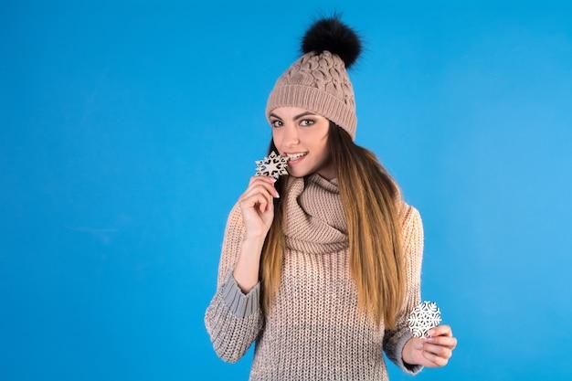Молодая женщина, держащая две блестящие снежинки