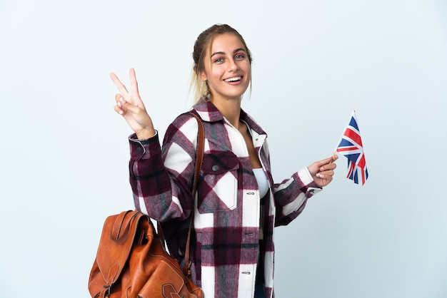 Young woman holding an uk flag isolated on white background smiling and showing victory sign
