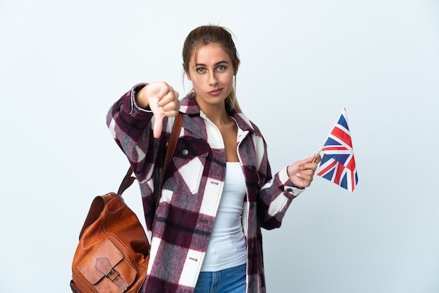 Young woman holding an uk flag posing isolated against the blank wall