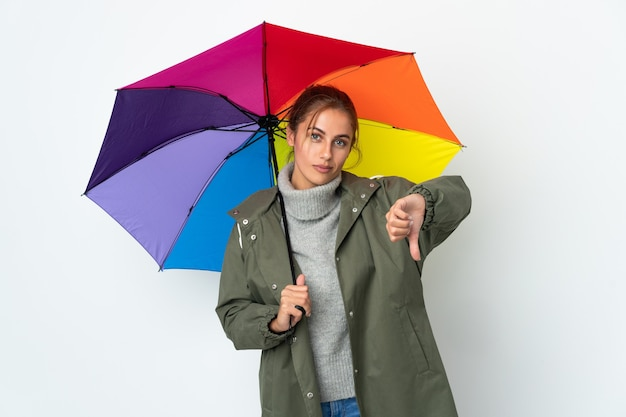 Young woman holding an umbrella isolated showing thumb down with negative expression
