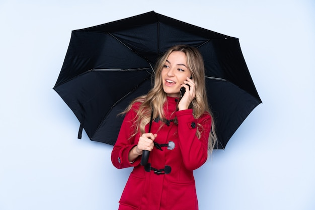 Young woman holding an umbrella over isolated wall