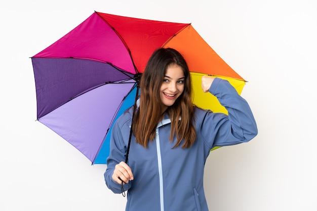 孤立したbakcgroundに傘を置く若い女性