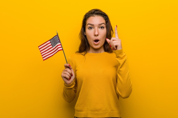 Young woman holding an united states flag having some great idea, concept of creativity.