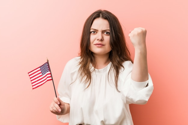 Young woman holding a united states flag showing fist