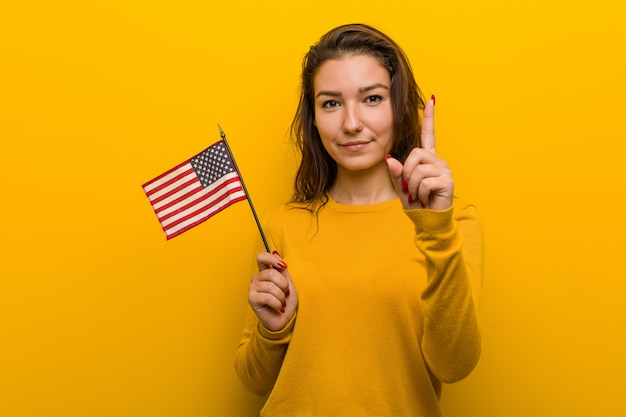 Young woman holding an united states flag showing number one with finger.
