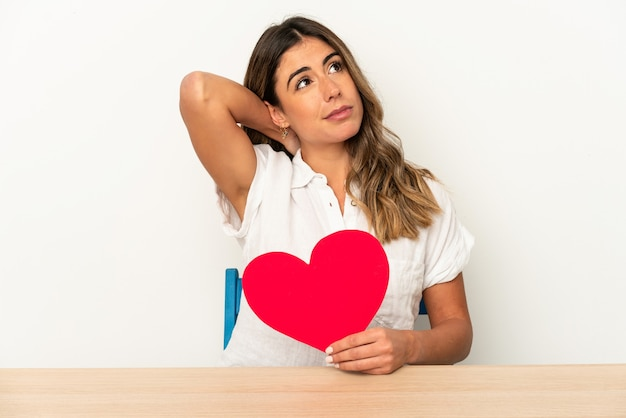 Young woman holding a valentines day card expressing emotions isolated