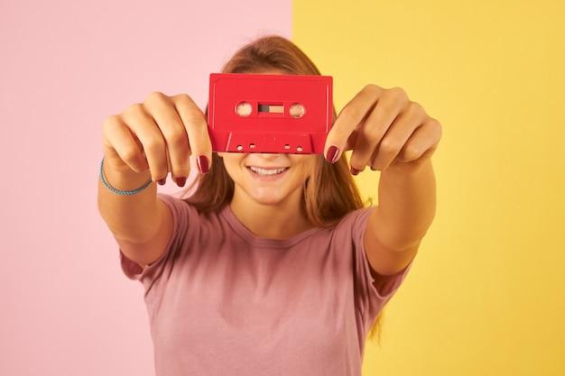 Молодая женщина, держащая винтажную аудиокассету