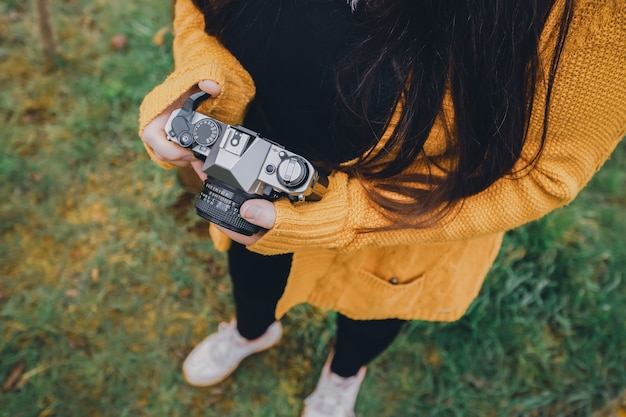 Young woman holding a vintage camera and standing on the grass