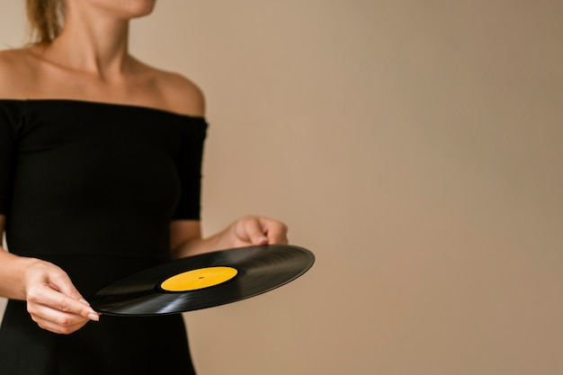 Young woman holding vinyl disk with copy-space