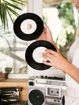 Young woman holding vinyl record disks near player