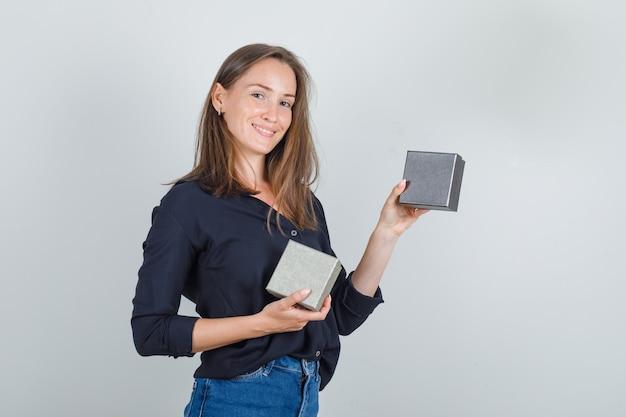 Giovane donna che tiene scatole per orologi in camicia nera, pantaloncini di jeans e sembra felice