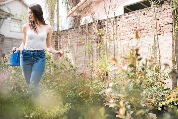 물을 들고 젊은 여자는 성장하는 식물 사이에 서 있습니다