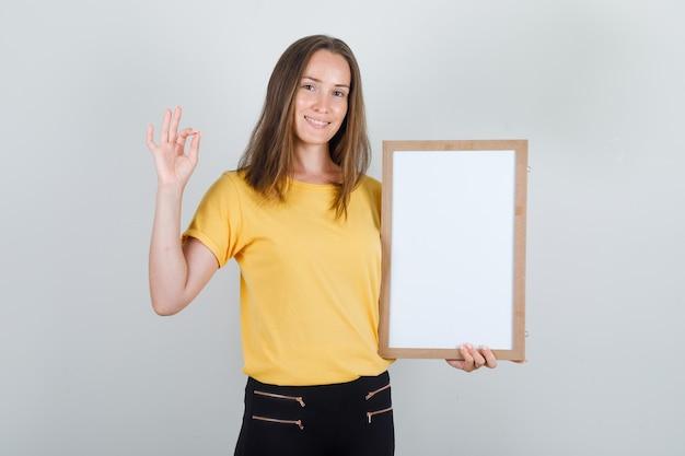 Tシャツ、ズボンでokサインとホワイトボードを保持し、嬉しそうに見える若い女性。