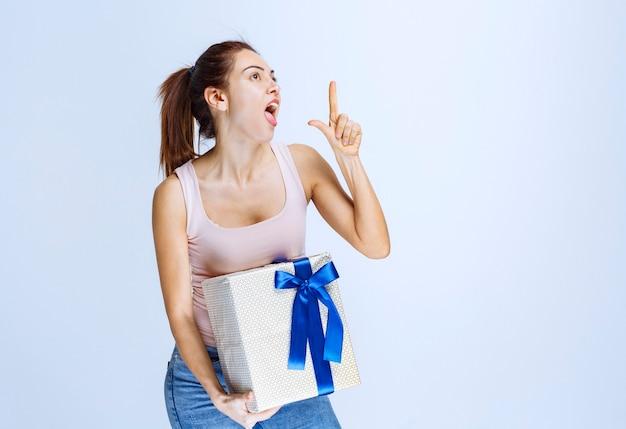 Giovane donna che tiene in mano una scatola regalo bianca avvolta con un nastro blu e lo dimostra