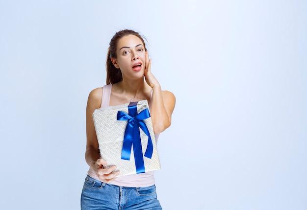 Giovane donna che tiene una scatola regalo bianca avvolta con un nastro blu