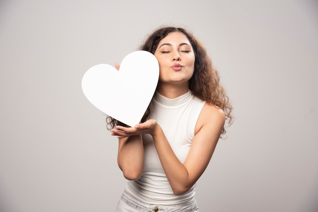 Young woman holding white handmade paper heart. high quality photo