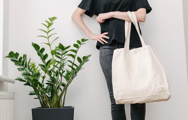 Молодая женщина, держащая белый тканевый эко-мешок против белой стены.