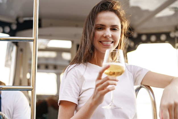 Young woman holding a wineglass and sitting on deck of sailing yacht