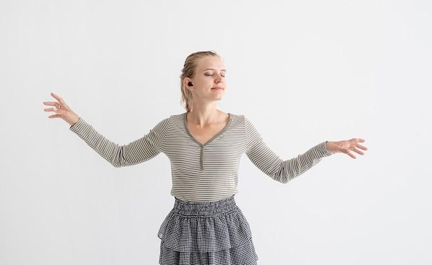 ワイヤレスイヤフォンを持って踊る若い女性