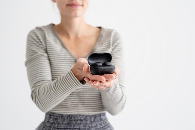 ワイヤレスイヤフォンを保持している若い女性