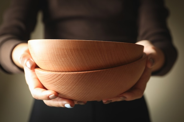 Young woman holding wooden bowls