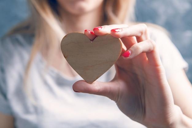 Молодая женщина, держащая деревянное сердце на сером