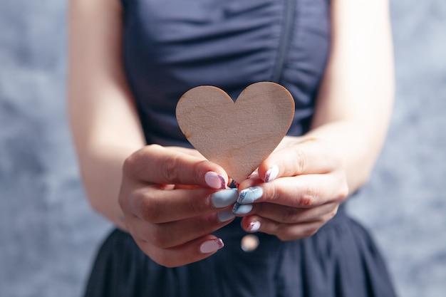 Молодая женщина, держащая деревянное сердце