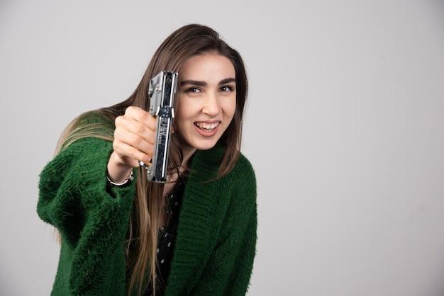 Una giovane donna in possesso di uno strumento di lavoro su uno sfondo grigio.
