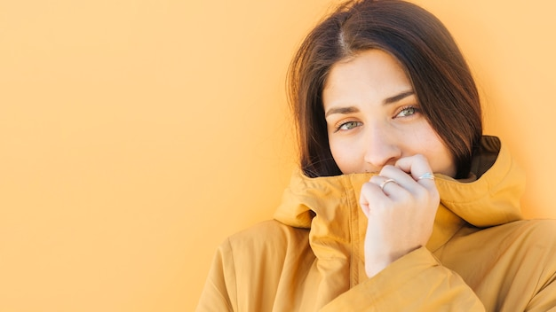 Young woman holding yellow jacket in front of her mouth looking at camera